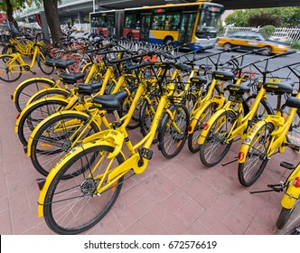 BEIJING, CHINA- JULY 2, 2017: A bus past next to a row of parked Ofo bicycles. Ofo, a bike-sharing company founded in 2014, has over 20 million registered users