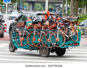 BEIJING, CHINA - JULY 22, 2017: A worker drives a truck loaded with Mobike bicycles in city downtown. Mobike was created by Beijing Mobike Technology Co., Ltd.