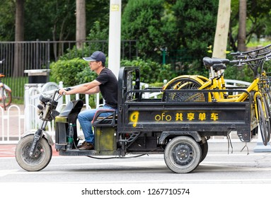 BEIJING, CHINA - JULY 22, 2017: An unidentified man drives a truck loaded with ofo bicycles in city downtown. Ofo, a bike-sharing company founded in 2014, has over 62.7 million montly active users