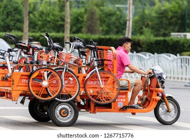 BEIJING, CHINA - JULY 22, 2017: An unidentified man drives a truck loaded with Mobike bicycles in city downtown. Mobike was created by Beijing Mobike Technology Co., Ltd.