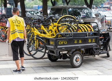 BEIJING, CHINA- JULY 23, 2017: An operator is seen next to a truck loaded with ofo bicycles at city downtown. Ofo is a bike-sharing company founded in 2014