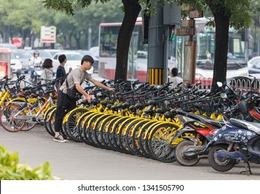BEIJING, CHINA- JULY 23, 2017: A man arranges ofo bicycles parked at a street downtown; ofo is a bike-sharing company founded in 2014
