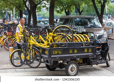BEIJING, CHINA- JULY 23, 2017: An unidentified man loads a truck with ofo bicycles in city downtown. Ofo is a bike-sharing company founded in 2014