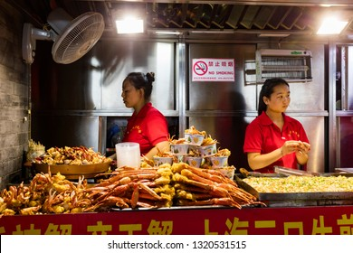 Beijing, China - July 27, 2017: People selling food on Wangfujing Snack Street in Dongcheng District of Beijing.