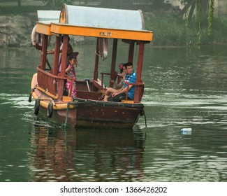Beijing, China - July 30, 2010: a family in a boat on a lake in Beijing pass a plastic bottle floating on the water but are oblivious to it