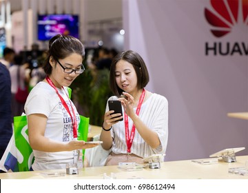 BEIJING, CHINA- JULY 9, 2017:  Visitors try modern mobile phones at the Huawei booth during the Beijing International Consumer Electronics Expo held in the China National Convention Center (CNCC).