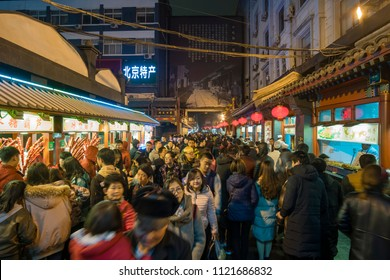 Beijing, China - Mar 17, 2018: People visiting the Wangfujing Snack Street in Beijing. It is a night market with many stalls selling street snacks.