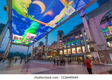 Beijing, China - Mar 18, 2018: People at a modern shopping mall in Beijing with a huge outdoor LED screen.