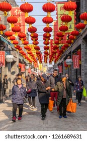 Beijing, China - Mar 18, 2018: Chinese walking an alley in Qianmen Shopping Street in Beijing. It is the oldest shopping street in Beijing.