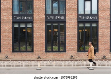 Beijing, China - Mar 23, 2018: Man walking pass a cafe at 798 Art Zone in Beijing. It is a district characterized by modern art and exhibition of Chinese culture and art.