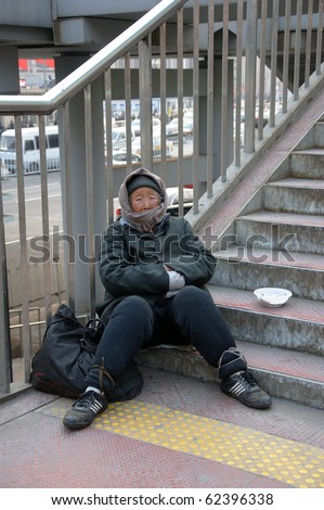 BEIJING, CHINA - MARCH 06: Unidentified old Chinese woman begs for money at the Train Station March 7, 2010 in Beijing, China. Shelter is hard to find for the poor even during the winter.