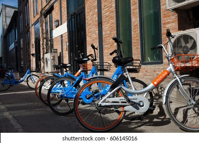 """Beijing, China - March 12, 2017: Many bicycles of """"Mobike"""" and """"Bluegogo"""" lined up. They are the most popular fully station-less bicycle-sharing system in the city of China."""