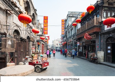 BEIJING, CHINA - MARCH 19, 2017: people on shopping street Dashilan West in Hutong Area in old town. Hutongs are narrow streets protected to preserve Chinese cultural history