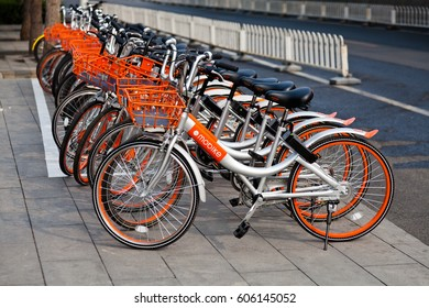 """Beijing, China - March 21, 2017: Many orange bicycles of """"Mobike"""" lined up. Mobike fully station-less bicycle-sharing system is one of the world's largest bicycle operator."""