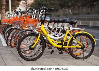 """Beijing, China - March 21, 2017: Many bicycles of """"Mobike"""" and """"Ofo"""" lined up. They are the most popular fully station-less bicycle-sharing system in the city of China."""