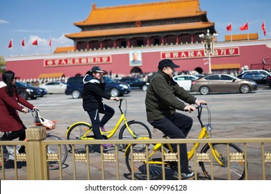 """Beijing, China - March 26, 2017: Three people ride """"Mobike""""  and """"Ofo"""" bicycle on Tiananmen Square.The most popular fully station-less bicycle-sharing system in China."""