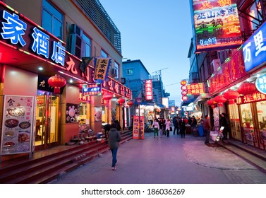 BEIJING, CHINA - MARCH 27:  Chinese people walks next to restaurants on one of the parallel street to famous Qianmen Dajie pedestrian commercial street on March 27, 2013 in Beijing