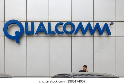 BEIJING, CHINA- MARCH 28, 2019: An unidentified man talks on the phone near a Qualcomm sign; Qualcomm is an American company founded in 1985.