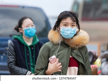 BEIJING, CHINA- MARCH 31, 2019: Unidentified women are seen wearing a face mask around Wangfujing area at city downtown.