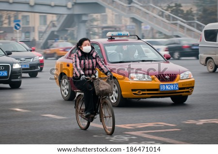 BEIJING, CHINA - MARCH 31: Woman with protective mask rides bike on a busy street in Dongcheng District on March 31, 2013 in Beijing