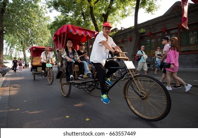 Beijing, China - May 21, 2017: Tourists riding the traditional rickshaw in old Hutongs