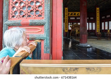 Beijing, China - MAY 9, 2017: An elder trying to watch the emperor throne by her own eyes from the fence preventing tourist vandalism