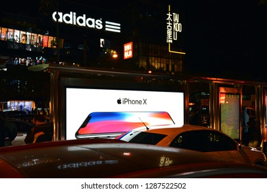 Beijing, China - November 11, 2017:  Night shot in Sanlitun, a busy shopping district, featuring billboard ad for release if iPhone X. Adidas and Uniqlo signage is also visible.