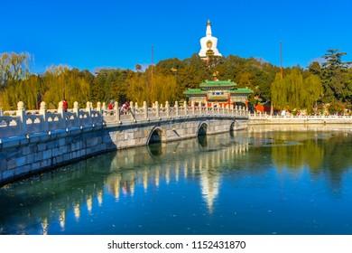 BEIJING, CHINA - NOVEMBER 27, 2017 Yongan Bridge Buddhist White Stupa Dagoba Gate Jade Flower Island Beijing China Beihai public park created  1000AD. Stupa built in 1600s.