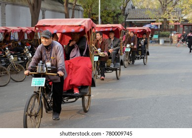 BEIJING, CHINA - NOVEMBER 9, 2017:  Cycle rickshaw, or pedicab, riders transport passengers on Beijing street.