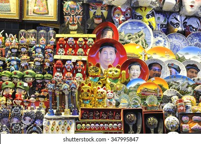 BEIJING, CHINA - OCT 19, 2014 - A souvenir stall at a Beijing night market selling Xi Jinping face plates and other kitsch rubbish.
