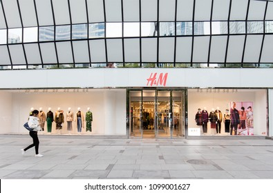 BEIJING, CHINA – OCTOBER 11, 2017: A woman walk past a H & M store; H & M Hennes & Mauritz AB (H&M), a Swedish multinational retail-clothing company, exists in 62 countries and as of 2015