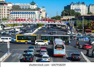 BEIJING, CHINA – October 15, 2013: panoramic view of central streets of Beijing, in foreground: intersection with a busy traffic, in the background: modern offices and houses with traditional roofs
