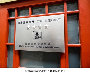 Beijing, China - October 18 2013:  Information sign on a red door, advising of a four star rated toilet in the Forbidden City, issued by the Beijing Tourism Administration, in Chinese and English