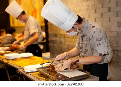 BEIJING, CHINA - SEPTEMBER 1, 2012: Chef are cutting roasted duck in a restaurant in Beijing,China on September 1, 2012.