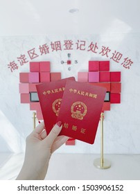 beijing, china- september 12,2019: a female hand holding a pair of Chinese marriage certificate, Chinese characters on wall means:Welcome to haidian district marriage registration office