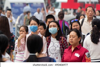 BEIJING, CHINA - SEPTEMBER 25, 2016:  Two women using face mask are seen among a crowd of people at Wangfujing Street, which is regarded as one of the busiest shopping streets in Beijing