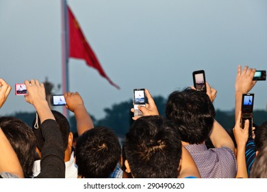BEIJING, CHINA - SEPTEMBER 9: Crowd shooting for Flag Landing Ceremony on September 9, 2012, Beijing, China. Honor guards hold a flag-raising flag-landing ceremony at dawn or dusk every day.