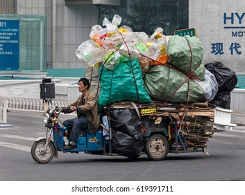 BEIJING, CHINA-APRIL 4, 2017: A man is seen on a freight bike loaded with recyclable materials. More than 7 billions plastic bags and 10 billion cardboard boxes were used for shipping parcels in 2015.