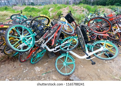 BEIJING CHINA-August 28, 2018: Urban wasteland is stacked with abandoned shared bicycles. Mobike, OFO, Yongan line, Hellobike and other brands. Too many bicycles in China's cities block traffic.