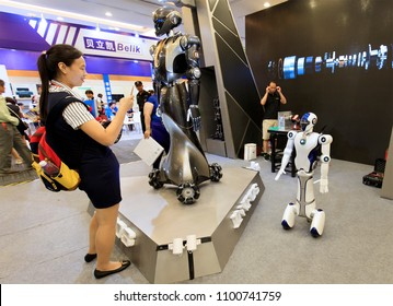 BEIJING, CHINA-JULY 2, 2017: An unidentified woman takes a look at a robot performance demonstration during the China Beijing International Smart City Expo 2017.