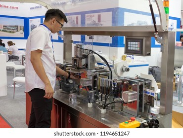 BEIJING, CHINA-JULY 29, 2017: A man operates an automatic packing machine during the China International Diet & Beauty Exhibition (CIDBE)