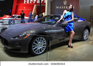 BEIJING, CHINA-MAY 2, 2012:  A model poses next to a Maserati GranCabrio car is on display at the 2012 Beijing International Automotive Exhibition (Auto China 2012)