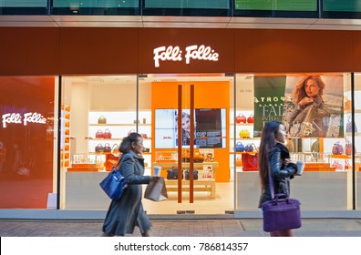 BEIJING, CHINA-NOVEMBER 22, 2014: Unidentified people walk past a Folli Follie store; Folli Follie Group is a Greek-based international company founded in 1982.