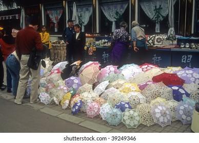 BEIJING - CIRCA NOV : Tourists shop for umbrellas on a rainy day circa November 2001 in Beijing.