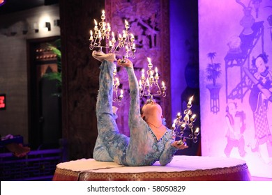 BEIJING - DECEMBER 3: Chinese girl performs candle acrobatics onstage at Dazhaimen hall on December 3, 2009 in Beijing, China