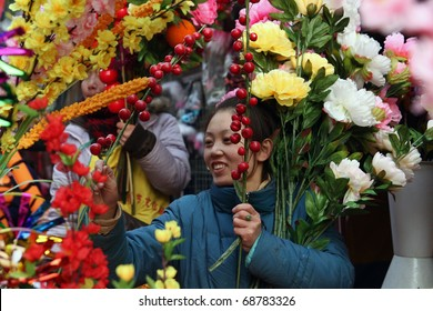 BEIJING - JANUARY 31: Young Chinese woman selling flowers at the Spring Festival Fair in Ditan Park in Beijing, January 31, 2009. The fair marked the beginning  or the Chinese Lunar New Year.