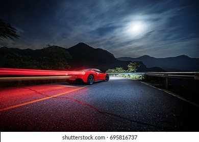 Beijing - June 07, 2017: Ferrari 488 on mountain road. Long exposure shot of red sports car with light trails from taillight. Illustrative editorial.