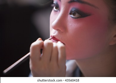 The Beijing opera actress is making up before the performance.