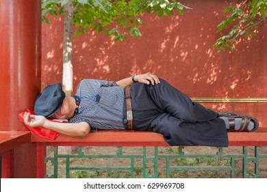 BEIJING-AUG. 23, 2010. Senior napping in a park. Sleeping in public is social accepted in China. Possible cause is notorious overwork, 60% of urban employees working more than 2 hours overtime daily.