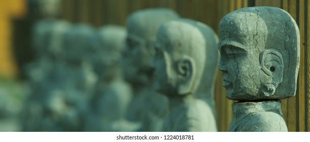Beijing/China - 10/29/2018: Stone Buddha statues stand outside a temple in Beijing. Buddhism is a growing religion in China, despite the Communist Party being atheist in nature.